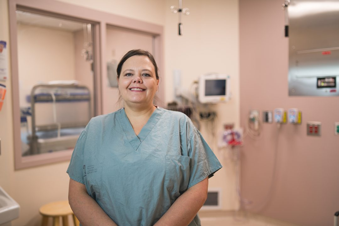 Gillyan Gravelle, registered nurse at Health Sciences North in Sudbury, Ontario, stands in a clinical room in the surgical area, wearing scrubs.