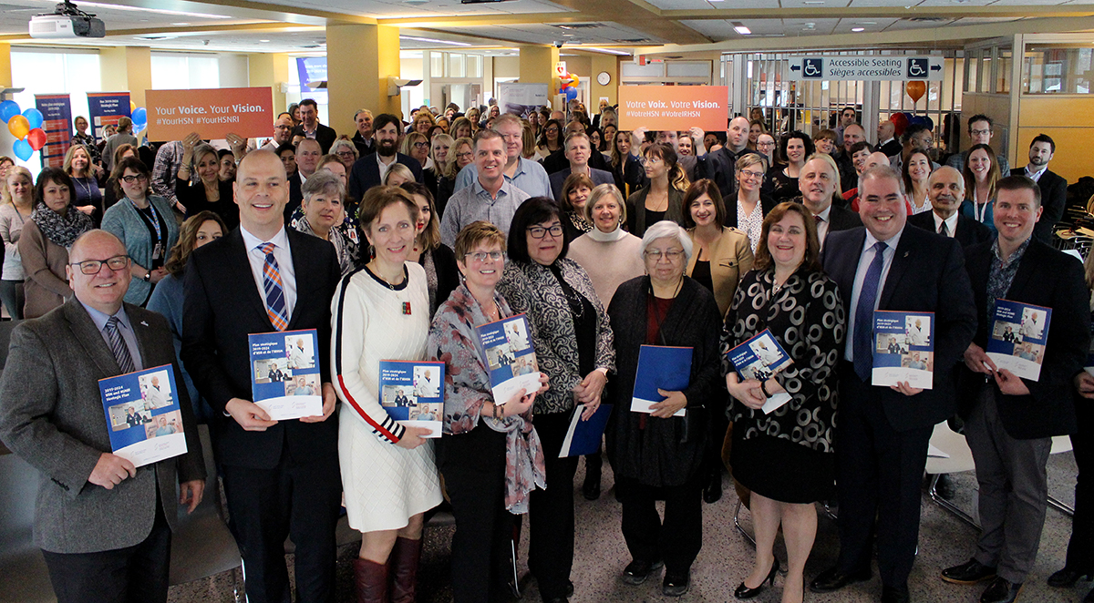 Crowd of people at Health Sciences North's cafeteria in Sudbury, Ontario, celebrating the launch of HSN and HSNRI's 2019-2024 strategic plan.